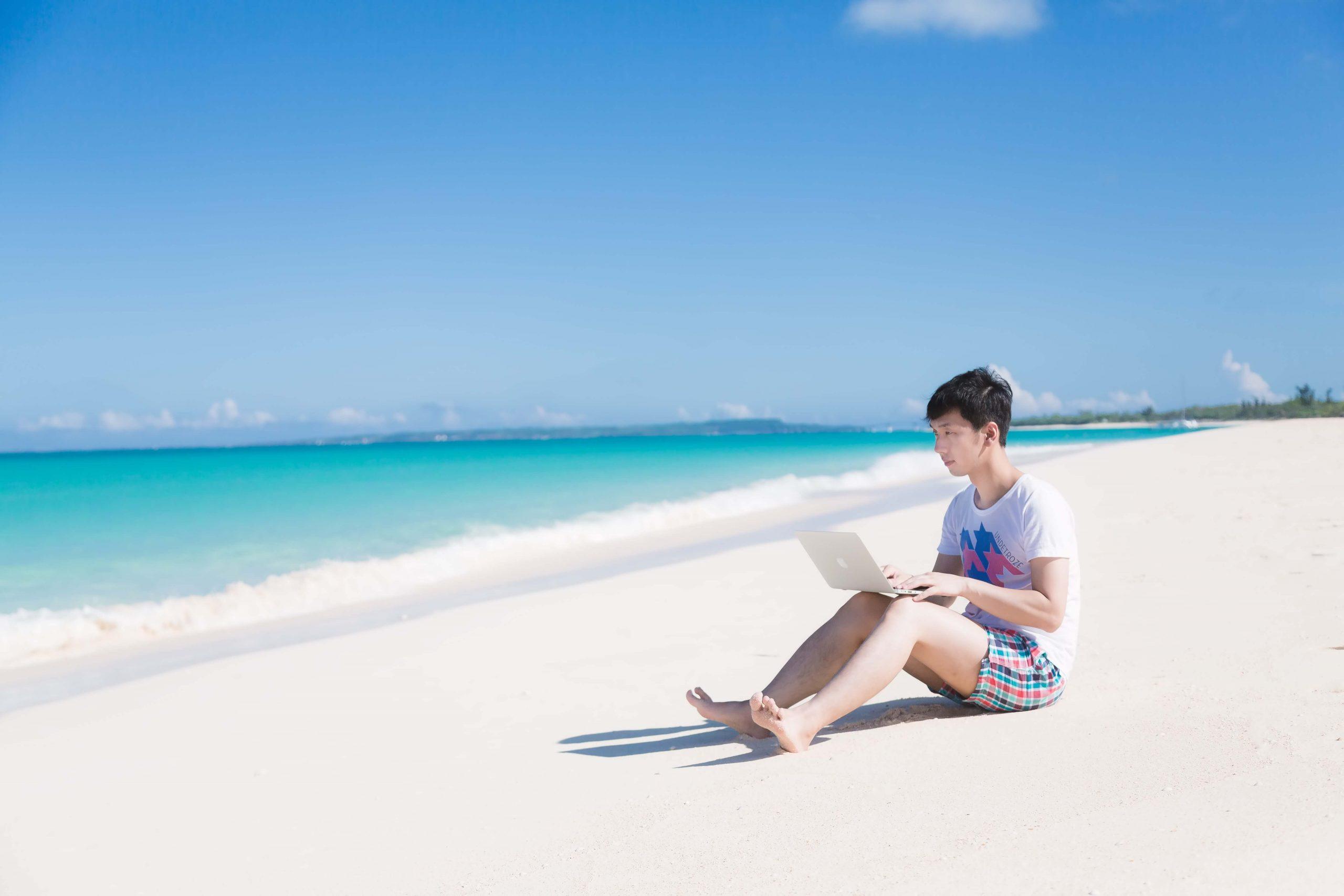 海岸でMacbookを使う男性