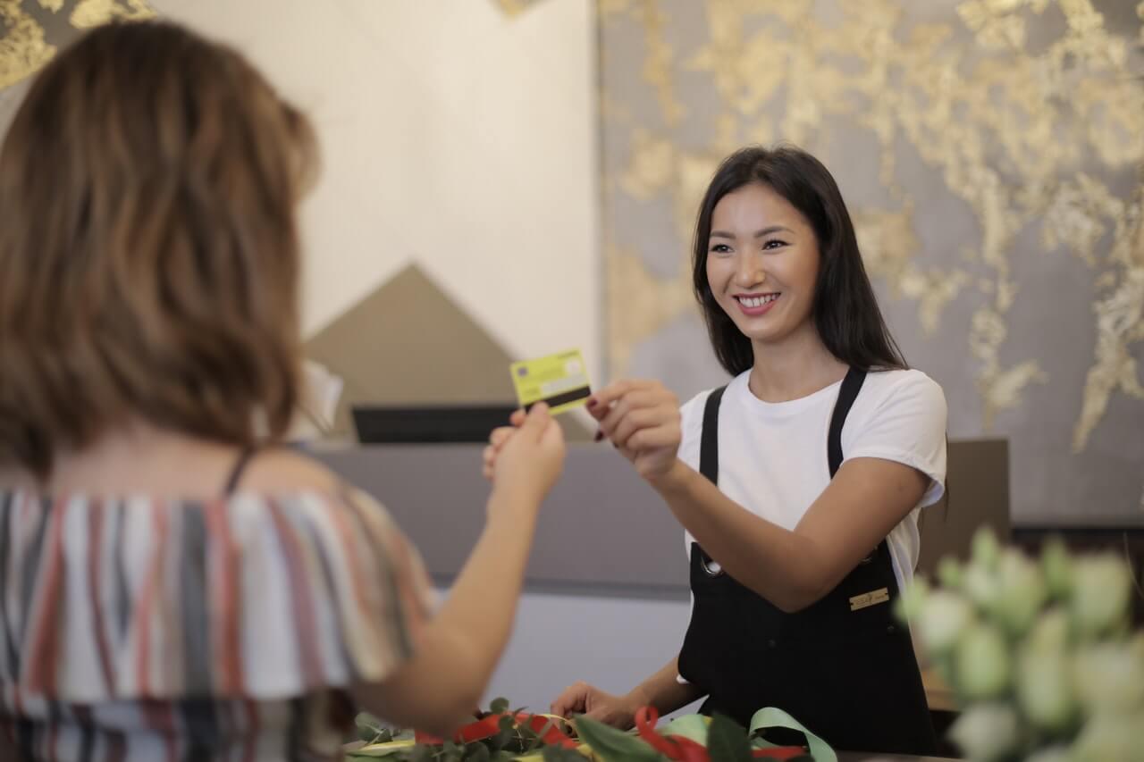 笑顔でクレジットカードを受け取る女性店員