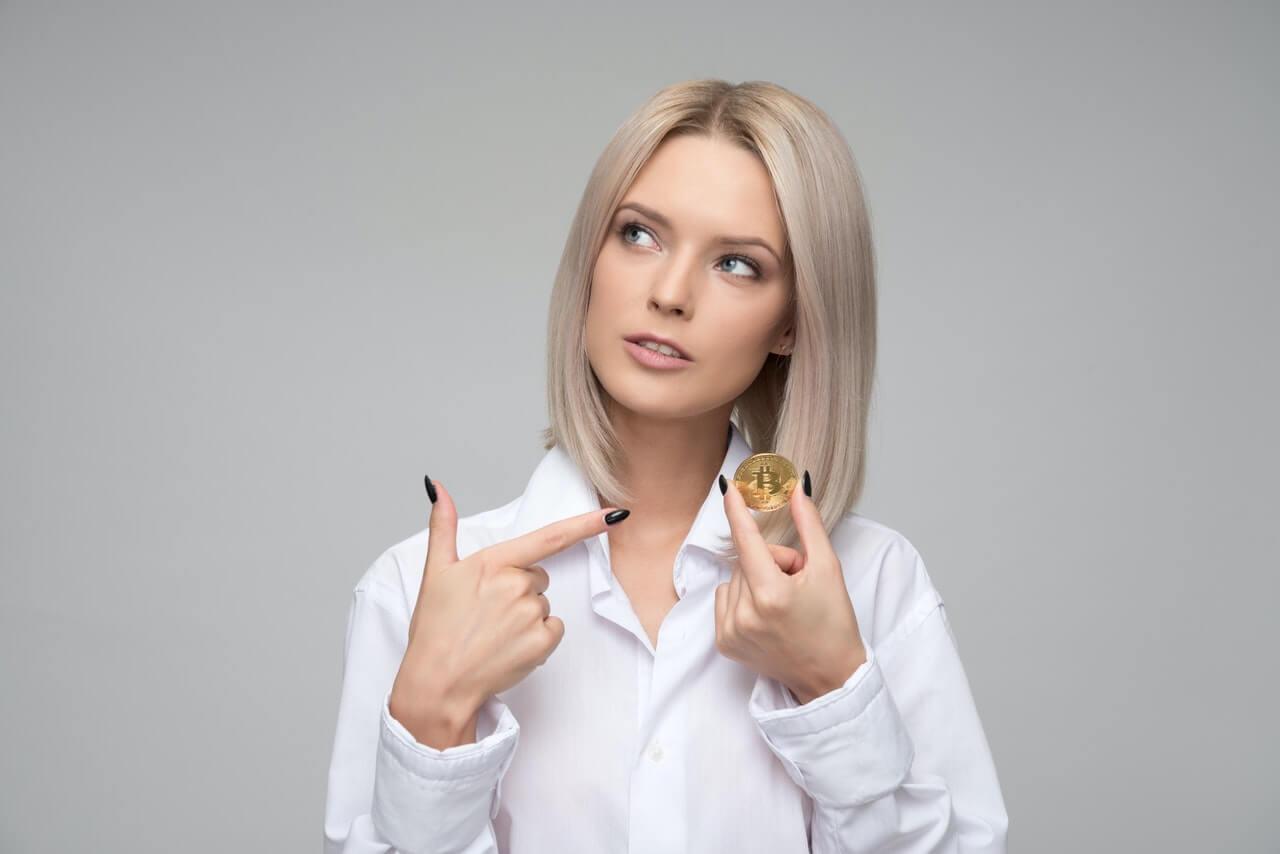 手に持ったコインを指さす女性